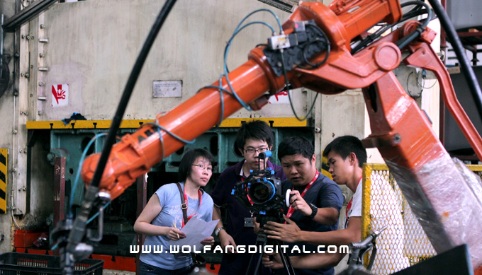 Pureen (our producer), reviews the last shot of a welding robot with our videographer and crew.